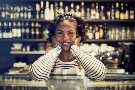 Smiling young African entrepreneur wearing an apron and leaning on the counter of her trendy cafe 版權商用圖片 - 101377519
