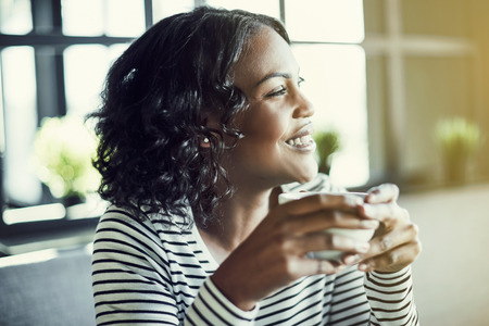 Smiling young African woman sitting alone at a table in a cafe enjoying a fresh cup of coffee and looking out the window