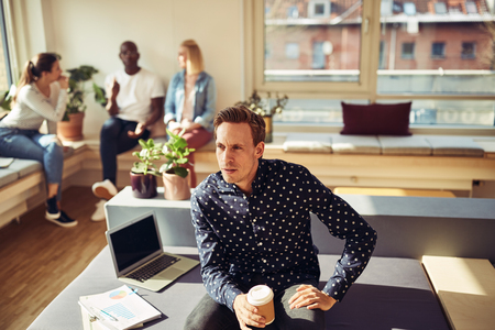 Focused manager sitting on his desk drinking a coffee and looking deep in thought while working in an office Stock Photo