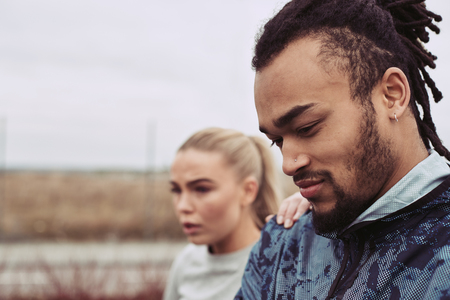 Young man catching his breath with his girlfriend standing in the background while out for a run together on an overcast day Stock Photo