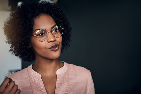 Smiling African businesswoman wearing glasses having a conversation with a work colleague in a modern office