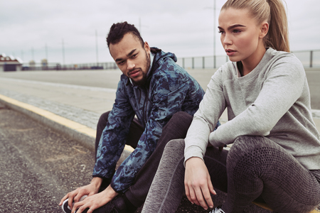 Diverse young couple in sportswear sitting on the side of a road taking a break from a run on an overcast day