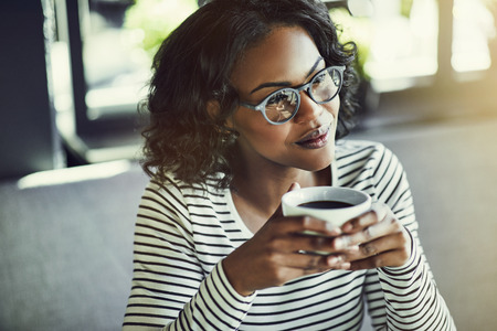 Young African woman wearing glasses smiling and sitting alone at a table in a cafe drinking a fresh cup of coffee Stok Fotoğraf - 101377830
