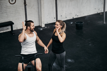 Two fit people in sportswear high fiving together after a stationary bike training session at the gym