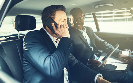 Businessman talking on his cellphone with a smiling colleague sitting next to him in the backseat of a car driving n the city