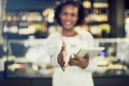 Young African hostess smiling and extending a handshake while standing in a trendy cafe holding a digital tablet Stock Photo