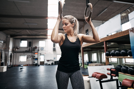 Fit young woman in sportswear sweating during a workout session with rings at the gym