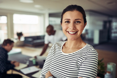 Smiling young businesswoman standing confidently with her arms crossed in an office with colleagues at work in the background Stock Photo