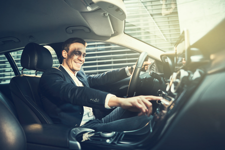 Smiling young businessman wearing a blazer changing radio stations while driving his car through the city during his morning commute to work Stockfoto