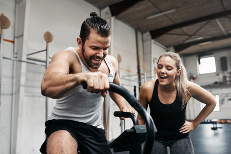 Smiling young woman cheering on her male friend riding a stationary bike during a workout session together at the gym Imagens