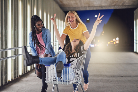 Two laughing young women pushing their girlfriend in a shopping cart along a walkway in the city at night