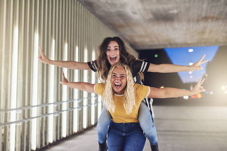 Laughing young woman being carried on her friends shoulders while enjoying a night out together in the city