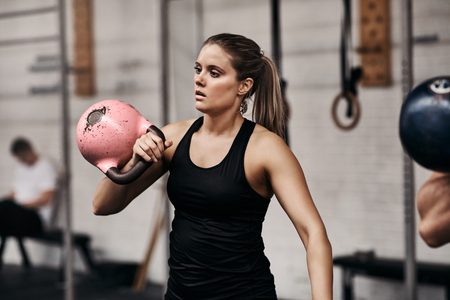 Focused young woman in sportswear lifting a dumbbell during a workout session with weights at the gym Фото со стока