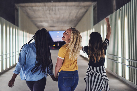 Laughing group of young women having fun while walking hand in hand together down a walkway in the city at night