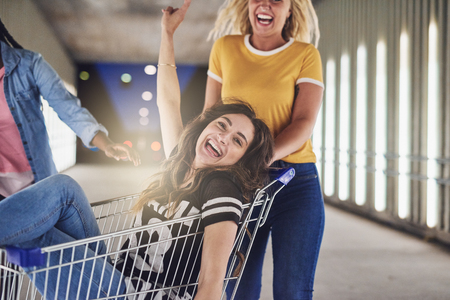 Laughing young woman being pushed along a walkway in a shopping cart at night in the city by two girlfriends