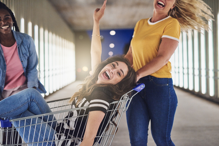 Laughing young woman sitting in a shopping cart being pushed along a walkway in the city at night by her two girlfriends