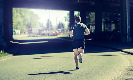 Rearview of a fit young man in sportswear listening to music on earphones while running under a bridge during an urban run