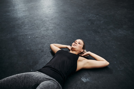 Fit young woman in sportswear doing sit ups on the floor of a gym during a workout session Stock Photo