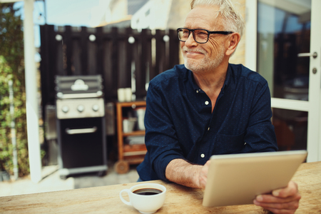 Senior man sitting at his patio table outside and smiling while working with a digital tablet and drinking a cup of fresh coffee