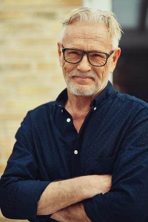 Lachende senior man met een baard en een bril staan met zijn armen gekruist buiten in zijn tuin thuis