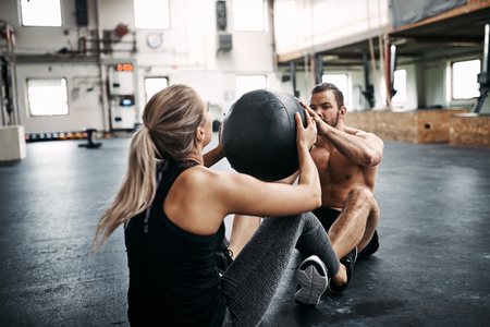 Fit young people in sportswear sitting together on the floor of a gym working out with a medicine ball during an exercise session