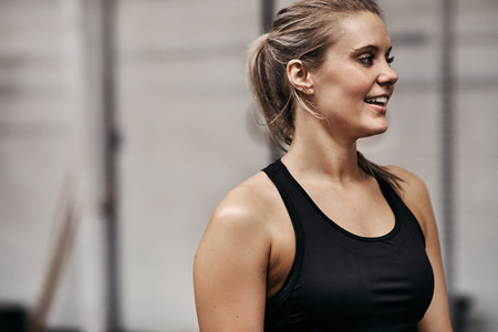 Fit young blonde woman in a sporty tanktop smiling while standing alone at the gym before a workout session Stock Photo