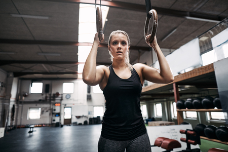 Fit young woman in sportswear focused on exercising on rings during a workout session in a gym