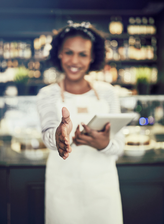 Welcoming young African hostess standing in a trendy cafe holding a digital tablet and extending her arm to shake hands Stock Photo