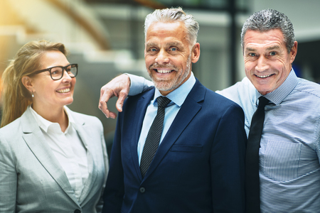 Smiling group of mature businesspeople standing happily together in the lobby of a modern office building