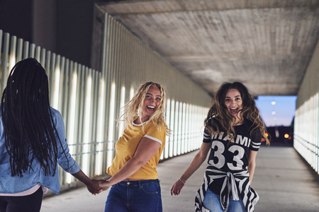 Carefree group of young girlfriends having fun together while walking along a walkway in the city at night