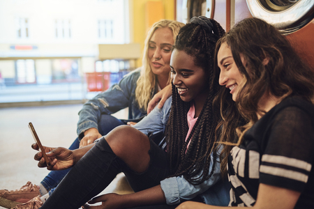 Diverse young female friends laughing while sitting together on the floor of a laundromat using a cellphone