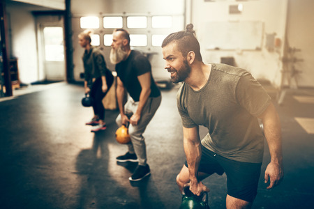 Group of fit people working out with dumbbells together during an exercise class at a gym