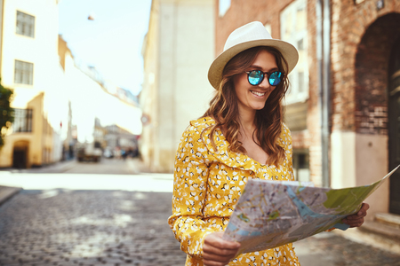 Smiling young brunette woman wearing a hat and sunglasses out exploring the city with a map