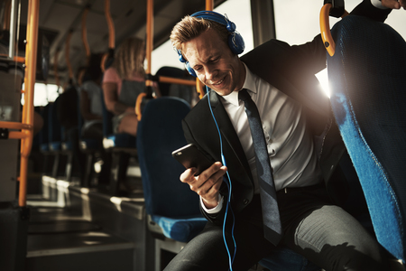 Young businessman smiling while sitting on a bus during his morning commute listening to music on headphones and using a smartphone Imagens