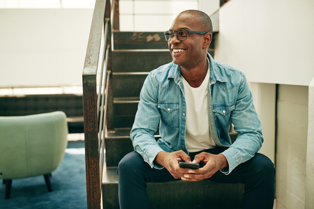 Smiling young African businessman wearing glasses and reading text messages on a cellphone while sitting on stairs in an office Stockfoto