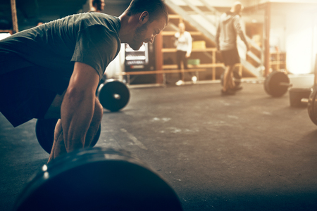 Fit young man straining to lift heavy weights on a barbell during a workout session in a gym