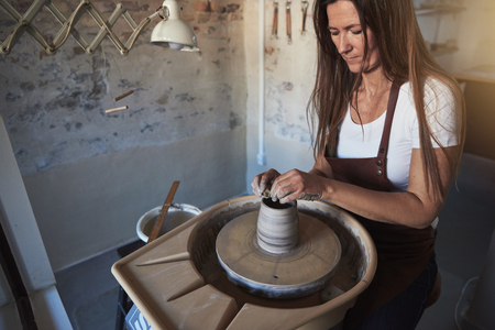 Female artisan sitting at a pottery wheel in her studio shaping a wet piece of clay with her hands