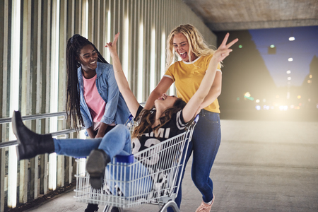 Two laughing young women pushing their friend in a shopping cart along a walkway in the city at night Banco de Imagens