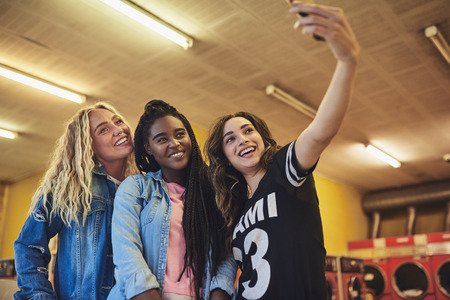 Smiling young female friends standing in a laundromat taking a selfie while doing laundry together