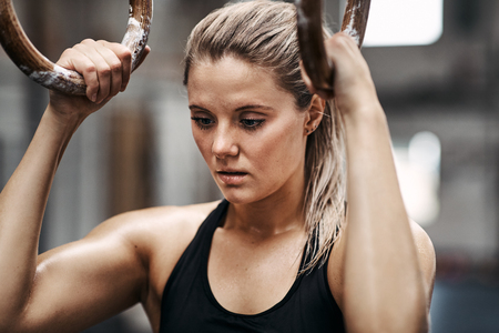 Fit young woman in sportswear getting focused before working out on rings at the gym