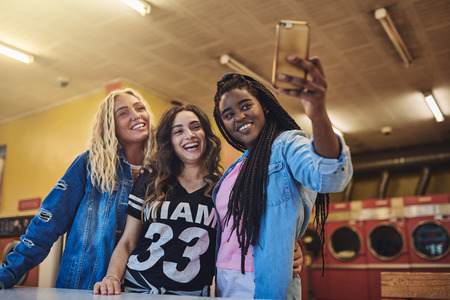 Smiling young female friends standing in a laundromat taking selfies while doing laundry together