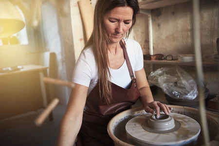Creative artisan sitting at a pottery wheel in her ceramic workshop using her hands to shape a wet piece of clay