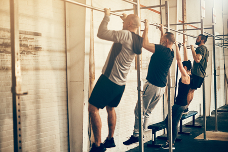 Group of fit people in sportswear doing chin ups during an exercise class together at the gym