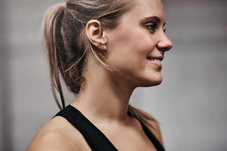 Smiling young blonde woman in a sporty tanktop standing alone in a gym before a workout session
