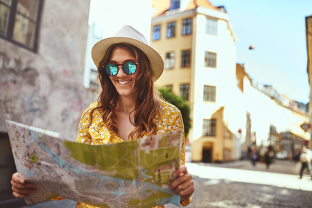 Smiling young brunette woman wearing sunglasses and a hat exploring the streets of a city with a map