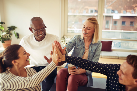 Diverse group of business colleagues high fiving each other while sitting together in a modern office