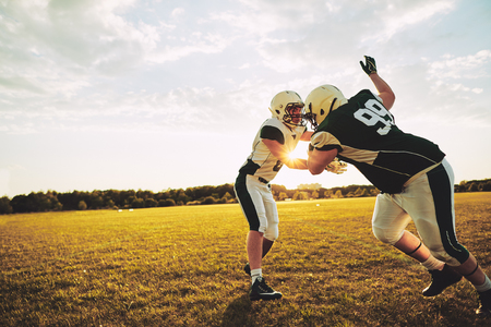 Young American football players doing tackling drills while practicing outside together on a grassy field in the afternoon