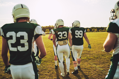 Group of young American football players walking together outside on a grassy field in the afternoon during a practice session