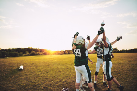 Excited group of American football players standing together in a huddle and raising a championship trophy in celebration Reklamní fotografie