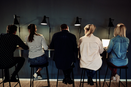 Rearview of a group of businesspeople working together while sitting in a row at a table in a dark office Banco de Imagens
